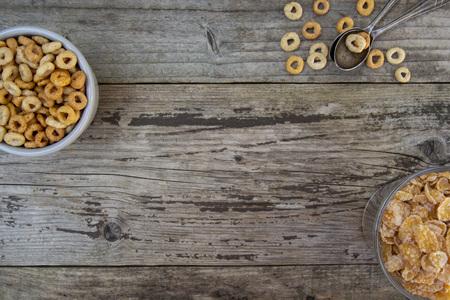 Cuenco con anillos de maíz y copos, desayuno de cereales. Fondo de textura rústica. Comida sana para niños.