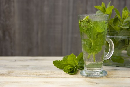 Summer fresh mint tea. Glass cup of green tea with mint leaves wooden background.