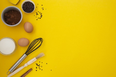 Ingredients for baking on yellow background - flour, wooden spoon, rolling pin, eggs, coccoa, sprinkles, banana. Top view, copy space. Baking utensiles.