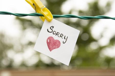 Es tut uns leid. Aufkleber mit trauriger Aufschrift und rotem Herz, das mit einer Wäscheklammer an einem Seil hängt. tut mir leid schriftzug