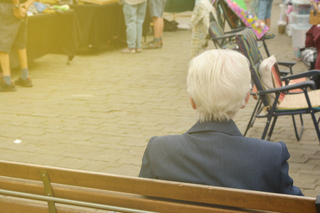 Back view of an old man, resting on bench, Stamford, England