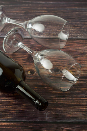 Dark bottle of wine and glasses on wooden background. Top view.