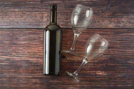 Dark bottle of wine and glasses on wooden