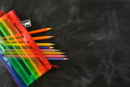Back to school. Rainbow pencil case with school supplies for student. Black background.