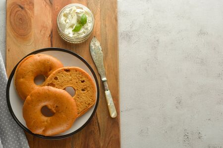 Delicious bagels with cream cheese on wooden board, pastry, bread for breakfast. Copy space.