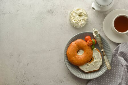 Breakfast with bagels and cheese, cherry, basil, tea cup. Healthy food, bright background