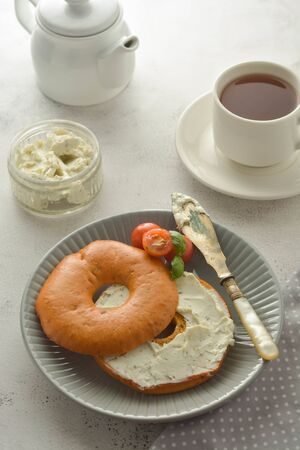 Breakfast with bagels and cheese, cherry, basil, tea cup. Healthy food, bright background. Banco de Imagens