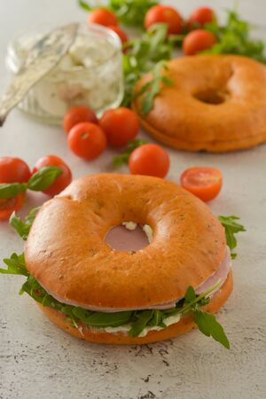 Healthy ham sandwich on a bagel with greens and tomato. Breakfast. Banco de Imagens