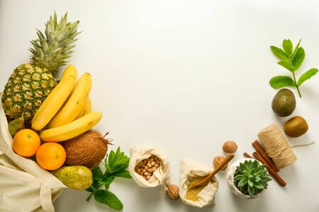 Zero waste concept, frame. Fruits and cereals in eco textile bags, glass jars with cereals, white background. Copy space.
