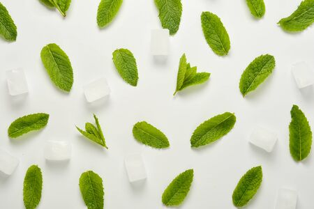 Ice cubes with mint leaves flat lay, isolated on white background.