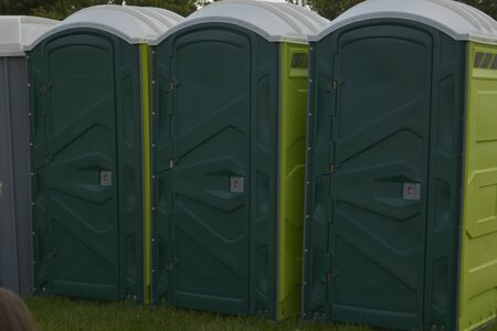 Row of mobile green bio toilets outside in the park.