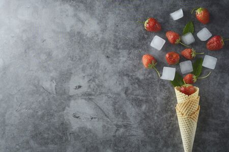 Strawberry fruits and mint leaves in waffle cone, over dark background, top view. Copy space.