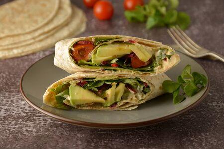 Tortilla wraps with avocado, cherry tomato. Healthy, vegan food. Take away snack, isolated 免版税图像
