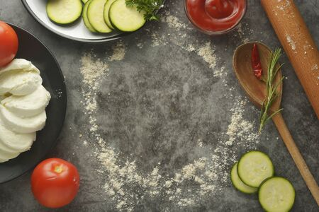 Round frame made of flour, rolling pin and vegetables - zucchini, tomatoes, ketchup, mozzarella on grey background, pizza cooking process.