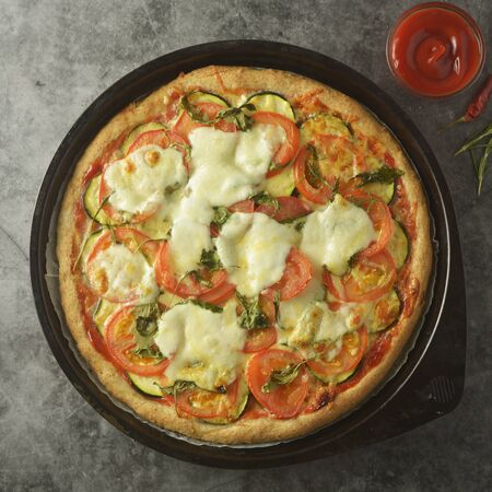 Vegetarian pizza with zucchini, tomatoes and mozzarella cheese. Healthy, dietical pizza.