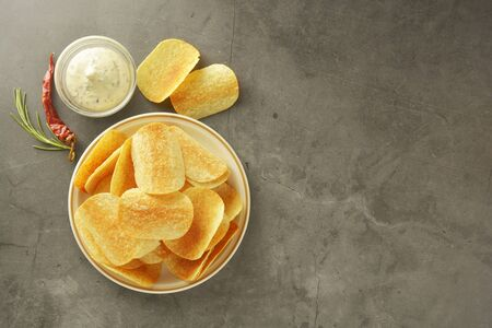 Crispy potato chips isolated over grey textured background. Flat lay.