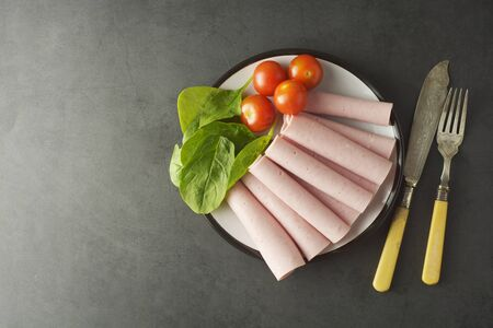Thin slices of ham rolled on plate with fresh vegetables, dark background. Breakfast food, ingredient for sandwich. Flat lay.
