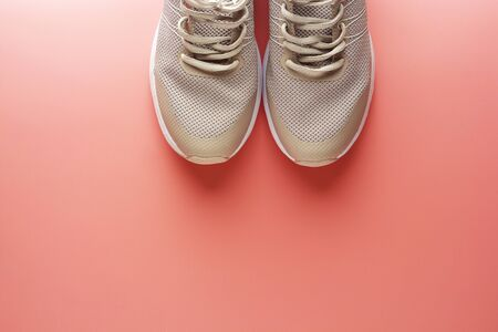 Flat lay of female sneakers, sport shoes on a pink background. Running workout, fitness, sport, yoga concept. Space for text.