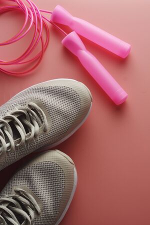 Sneakers, sport shoes and jumping rope over pink background. Health, running workout, fitness and yoga concept. Space for text.