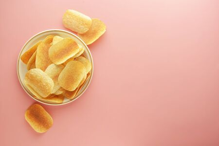 Crispy potato chips isolated over pink background. Flat lay. Stock Photo