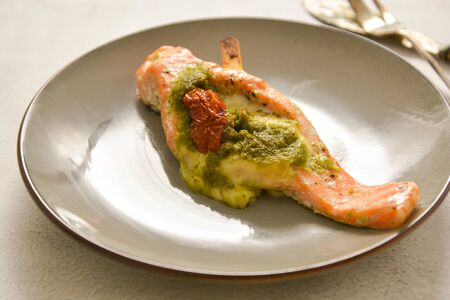 Baked salmon with cherry and pesto, isolated in stylish plate. Healthy foods. Stock Photo