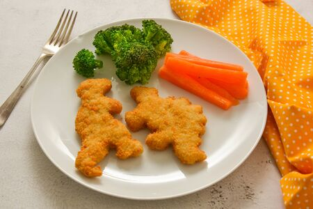 Kids food. Dinosaur shaped chicken, fish or turkey nuggets, ready to eat.