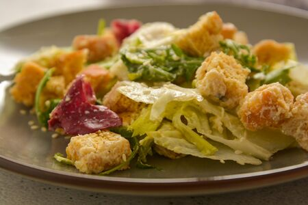 Healthy salad, caesar salad with croutons and dressing. Healthy food, dinner.