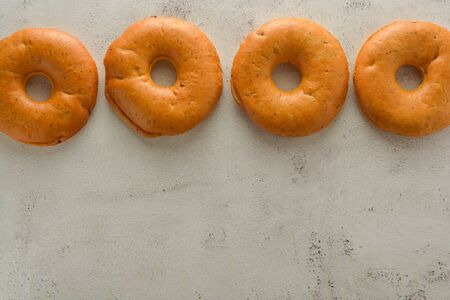 Bagels isolated on bright and textured board. Copy space. Stock Photo