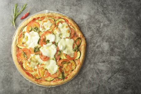Vegetarian pizza with zucchini, tomatoes and mozzarella cheese. Healthy, dialectical pizza.