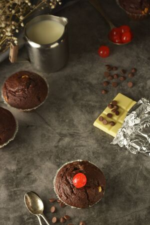 Chocolate muffins on dark background. Milk and chocolate isolated.