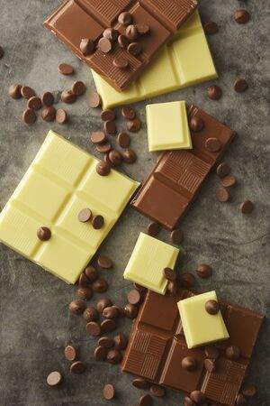 White and milk chocolate isolated. Top view of various chocolate bars, copy space.