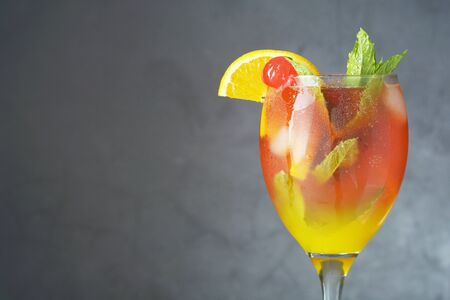 Summer cocktail. Orange juice with mint, syrup, fruit slices and ice. Dark background, copy space. Stock Photo