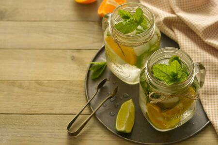 Homemade lemonade with lime, mint in a mason jar on a wooden rustic board.