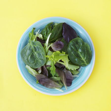 Fresh mixed green salad in round plate, yellow background. Healthy food, diet concept. Top view, square image.