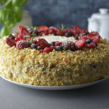 Homemade sponge cake with cream and fresh berries. Carrot and orange cake, decorated with berry. Stock Photo