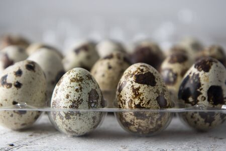 Quail eggs over white wooden background. Isolated quail raw eggs. rustic style. Healthy food ingredient.