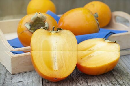 fresh khaki fruit isolated, sliced in half, on rustic table. Healthy food concept. Stock Photo