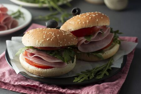 Hamburger with ham. Two burgers, homemade food. healthy sandwich with fresh vegetables on black plate. Stock Photo