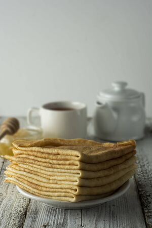 Pancakes. Thin pancakes.Healthy tasty breakfast - pancakes, a cup of tea and honey. Rustic background.