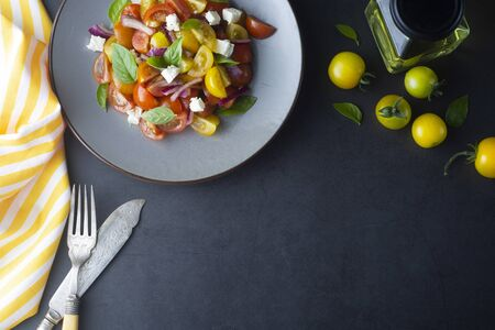 Colorful cherry tomatoes and basil salad on iin a plate, dark background. Healthy food frame. Cooking process.