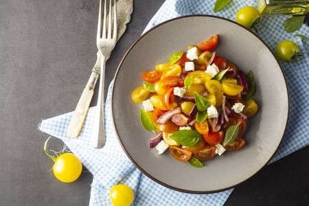 Colorful tomatoes and basil salad on a plate, dark background. Healthy, summer food.