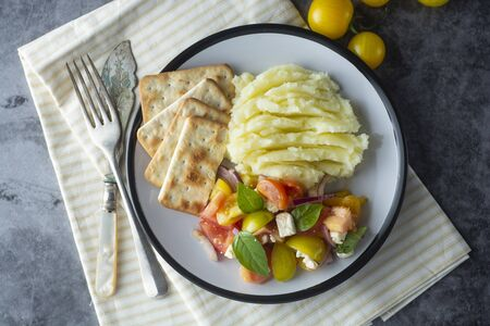 Tomatoes fresh salad and mushed potatoes in a plate. Healthy food.