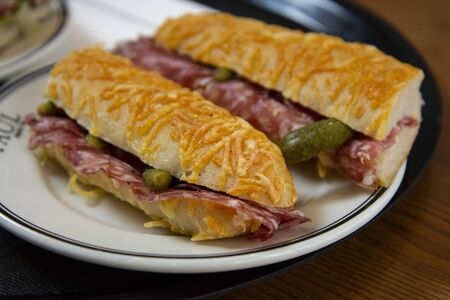 delicious baguette sandwich with ham and salami served on a plate in a bekery shop or cafe.