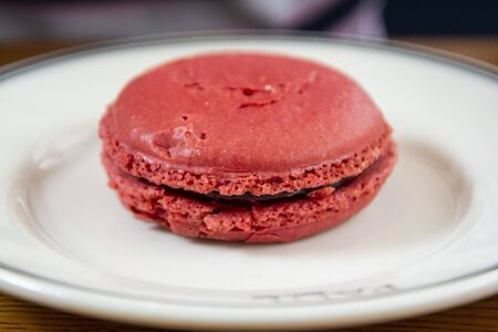 Big fresh pink macaroon with raspberry, round cake cookie, in a plate. Фото со стока