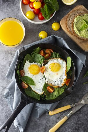 Fried sunny eggs with spinach, avocado toast and fresh tomatoes. healthy breakfast. Фото со стока