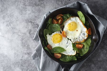 Fried egg on a pan served with fresh cherry tomatoes. Healthy food.