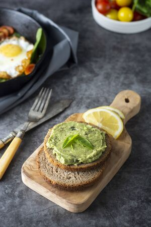 Appetizing guacamole, avocado pasta sandwich. Mexican guacamole. Green snack from avocado. Фото со стока