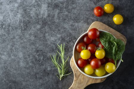 Fresh, organic yellow and red tomatoes in plate over dark background.