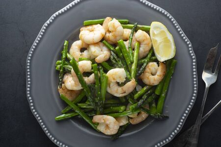 Salad from shrimp and green asparagus. Healthy seafood salad in plate. Top view, dark background. Stockfoto