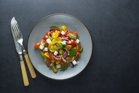 Colorful cherry tomatoes and basil salad in a plate, dark background. Healthy food. Фото со стока